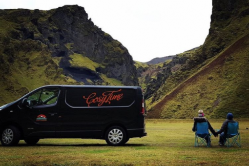 couple sitting next to camper in Iceland