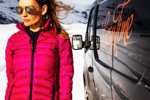woman standing next to camper in Iceland