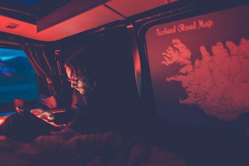 man reading inside a camper at night