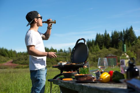 man outside barbecueing and drinkin beer
