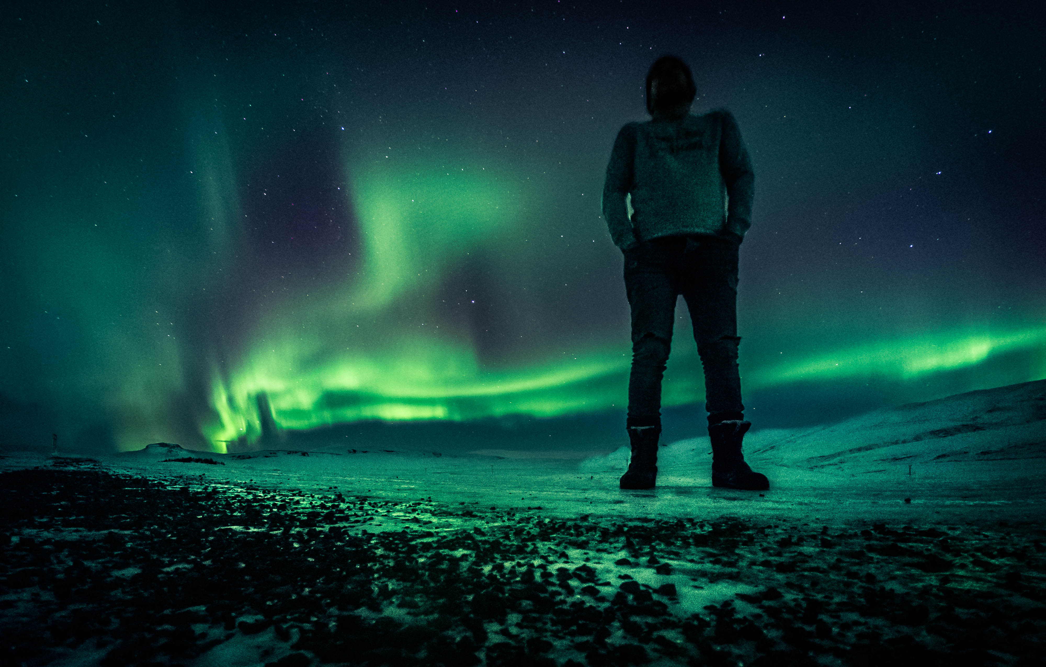man standing outside under the Norhern Lights